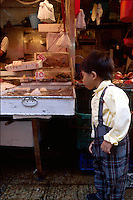 A young boy checks out fish for sale at the wet market, Hong Kong, China.