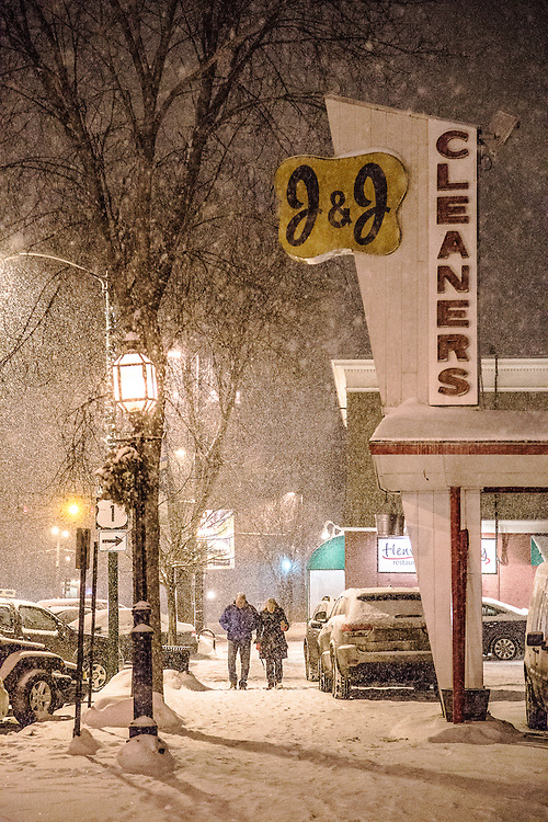A couple walks down the sidewalk on a snowy winter night in Brunswick, Maine.