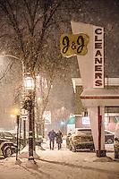 A couple walks down the sidewalk on a snowy winter night in Brunswick, Maine.