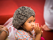 08 JANUARY 2015 - BANGKOK, THAILAND: A child meditates on Sanam Luang in Bangkok. Buddhist in Bangkok have a chance to meditate in front of seven large statues of revered Buddhist monks and worship a hair relic of the Buddha at a series of altars on Sanam Luang near the Grand Palace in Bangkok.    PHOTO BY JACK KURTZ