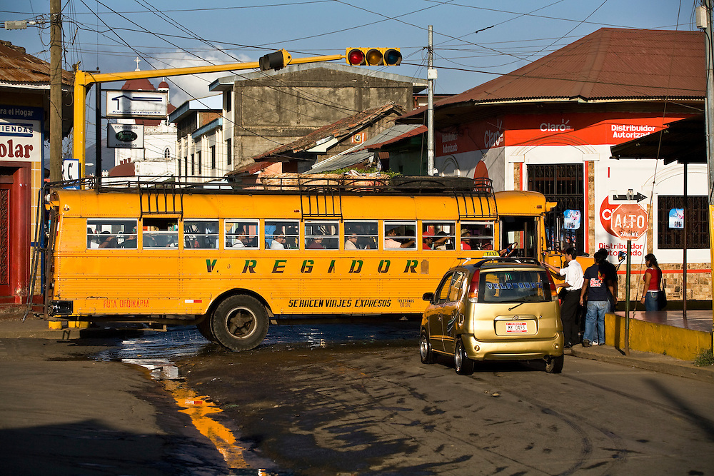 A local bus passes a taxi at a junction in Masaya. Masaya is located close to Granada, Nicaragua. It is a regional transportation hub and a famous market town where the products of the artisans of the surrounding towns are sold.