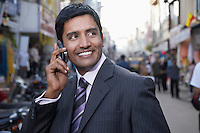 Business man using cell phone on city street smiling