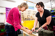 DEXTER, ME - AUGUST 4, 2015:  Sue Nordman (right), owner of Erda Handbags, explains the procedure for sewing their new prototype for a men's shave kit to her employee Lauri Maquillan (left 54 years old). Since most of Erda's employees are 60 years or older they have implemented a flexible scheduling system and invested in more ergonomic machines to accommodate their aging workforce. <br /> Craig Dilger for The New York Times