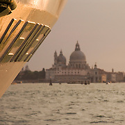 Ship tied-up alongside the Riva Dei VII Martiri on the Canale di San Marco with the Basilica di San Marco in the distance at sunset, Venice, Italy<br />