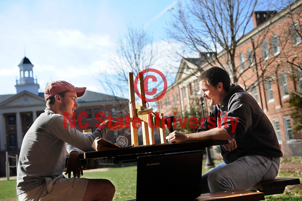 Mechanical Engineering junior Ryan Farlow, left, and Mechanical Engineering senior Andrew Mullican work on a projectile launcher for a dynamics class. They were working in the courtyard in Honors Village.