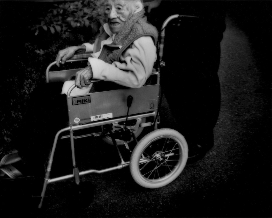 Homeless on streets / Streets like a nursing home: A woman, likely over 100 years old, is wheeled carefully on a central Tokyo street.  Japan.  Elderly and unemployed women are more likely to be taken in by family members than are elderly men and so, while it is common to see elderly homeless men, it is rare to see elderly homeless women.