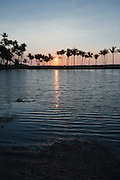 The setting sun reflects in Anaehoomalu Bay on the Big Island of Hawaii.