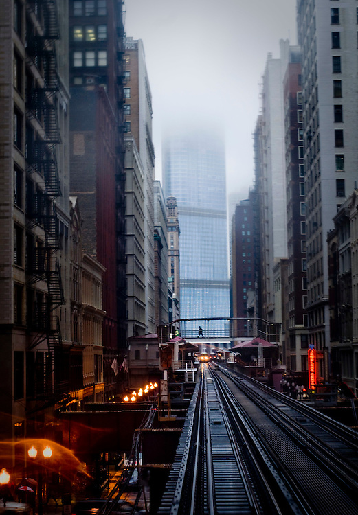 A man crossing a bridge over the L-train tracks on the Loop in Chicago. The Trump Tower in rain clouds in the background.<br /> <br /> <br /> <br /> Green Chicago..Photographer: Chris Maluszynski /MOMENT