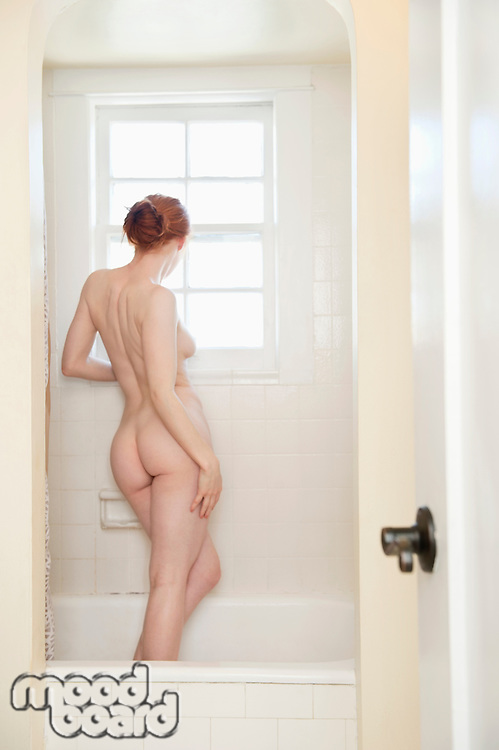 Back view of a sensuous young woman in bathtub looking through window