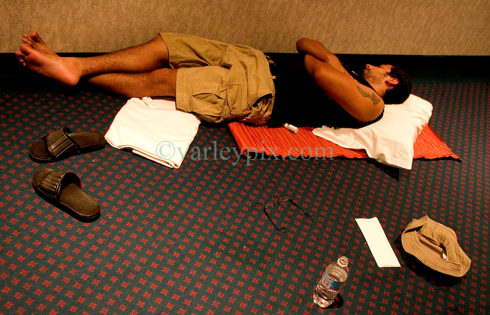 07 Sept 2005. New Orleans, Louisiana. Hurricane Katrina aftermath.<br /> <br /> Miami Herald's David Ovalle catches some sleep on the floor at the Hyatt from Hell in downtown New Orleans. Photo; &copy;Charlie Varley/varleypix.com