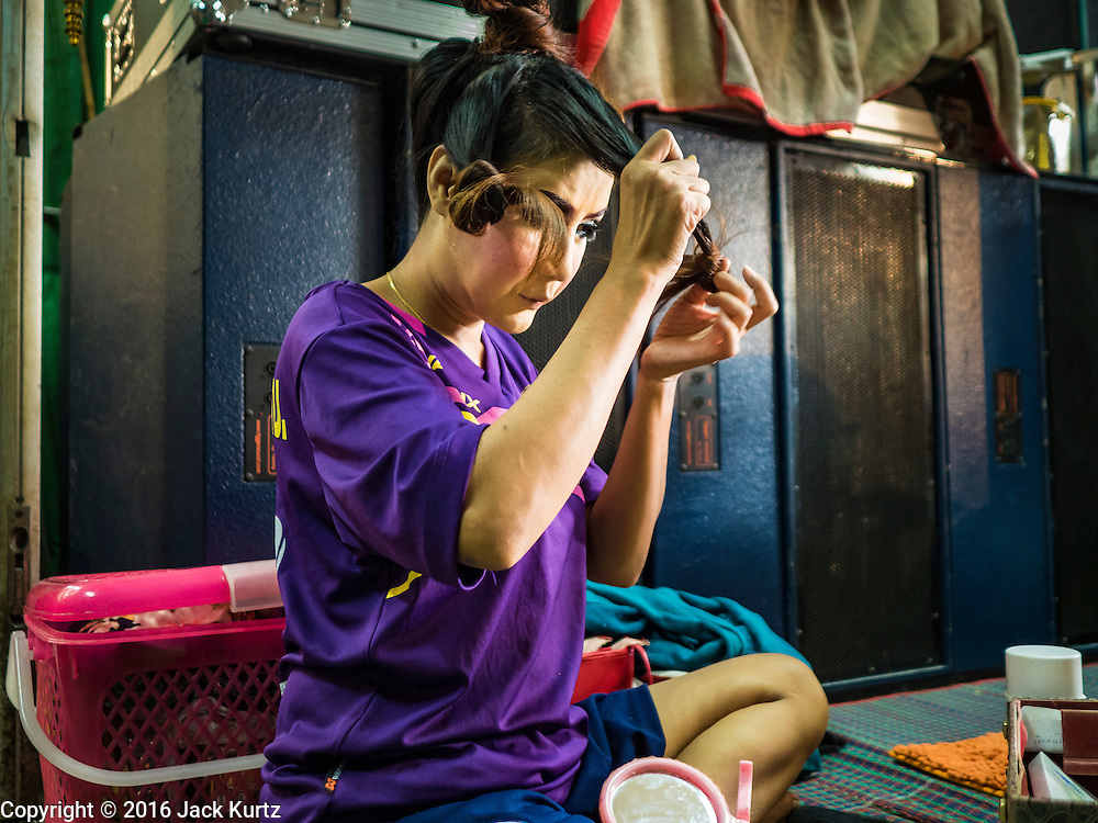 """30 JANUARY 2016 - NONTHABURI, NONTHABURI, THAILAND: A woman fixes her hair before a """"likay"""" show at Wat Bua Khwan in Nonthaburi, north of Bangkok. Likay is a form of popular folk theatre that includes exposition, singing and dancing in Thailand. It uses a combination of extravagant costumes and minimally equipped stages. Intentionally vague storylines means performances rely on actors' skills of improvisation. Like better the known Chinese Opera, which it resembles, Likay is performed mostly at temple fairs and privately sponsored events, especially in rural areas. Likay operas are televised and there is a market for bootleg likay videos and live performance of likay is becoming more rare.     PHOTO BY JACK KURTZ"""