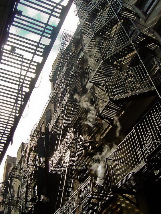 Alleys and fire escapes are one of Manhattans trademarks. This one is one of the very few left that has the old vintage feel to it. Steam from the nearby textile factorys escape through the vents .