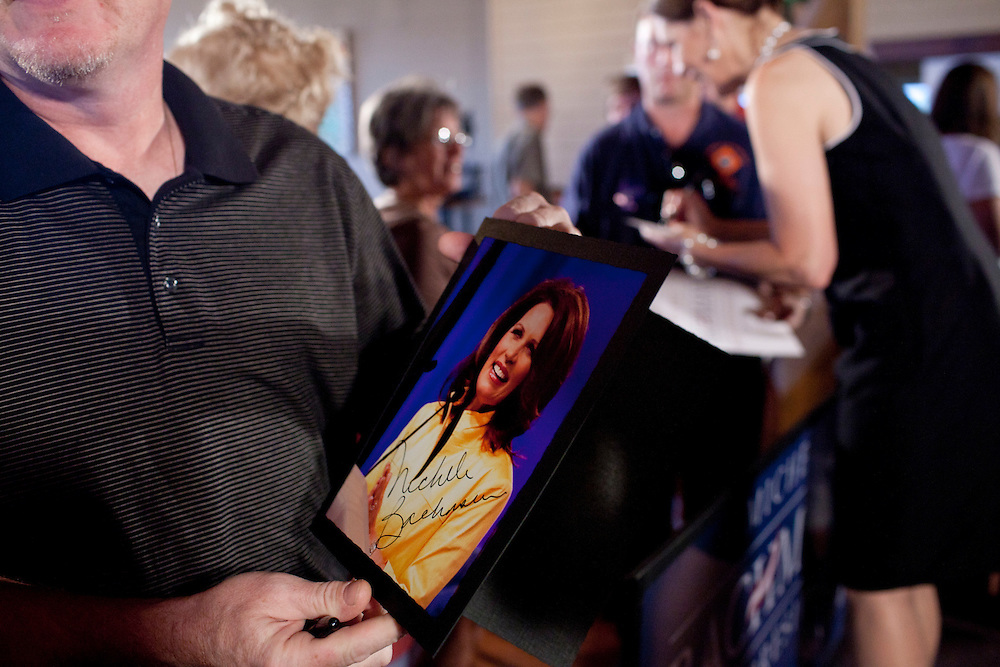 A man holds an autographed picture of Republican presidential hopeful Michele Bachmann as she campaigns on Sunday, July 24, 2011 in Muscatine, IA.