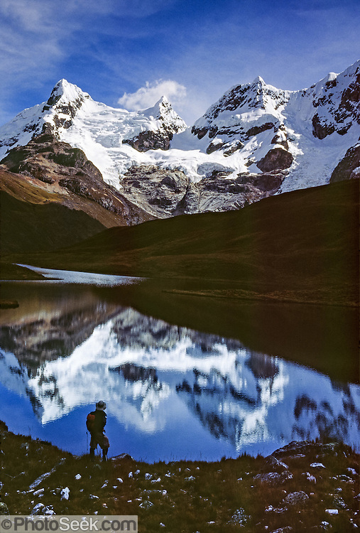 A trekker admires glacier covered peaks of the Cordillera Huayhuash reflecting in a lake at 15,000 feet elevation in the Andes Mountains, Peru, South America.