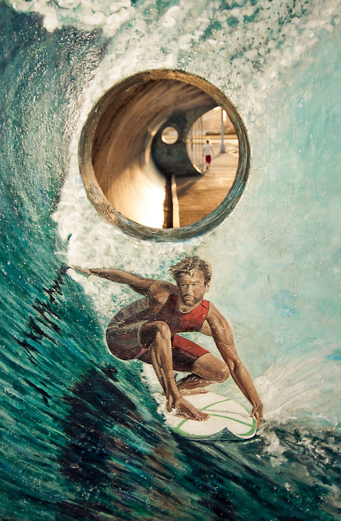 A mural of a surfer graces the side of a bus shelter and a child is seen walking down the sidewalk through an opening, Rockaway Beach, Queens, NY.
