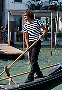 "Gondolier. Gondolas are traditional, flat-bottomed rowing boats which ferry people through Venetian canals. From a peak of 10,000 gondolas 200 years ago, just 500 gondolas now serve Venice. The banana-shaped modern gondola was developed in the 1800s. The left side of the gondola is made longer than the right side to resist leftwards drift at the forward stroke. The gondolier stands on the stern facing the bow and rows just on the right side, with a forward stroke and compensating backward stroke. The oar or rèmo is held in an oar lock, or fórcola, shaped for several rowing positions. The decorative fèrro (meaning iron) ornament on the front can be made of brass, stainless steel, or aluminum, as counterweight for the gondolier standing near the stern. The six horizontal lines and curved top of the ferro represent Venice's six sestieri (districts) and the Doge's cap. Painting gondolas black originated as a sumptuary law eliminating ostentatious competition between nobles. Until the early 1900s, many gondolas had a small cabin (felze) with windows which could be closed with louvered shutters--the original ""venetian blinds."" The romantic ""City of Canals"" stretches across 117 small islands in the marshy Venetian Lagoon along the Adriatic Sea in northeast Italy, Europe. Venice and the Venetian Lagoon are honored on UNESCO's World Heritage List. For licensing options, please inquire."