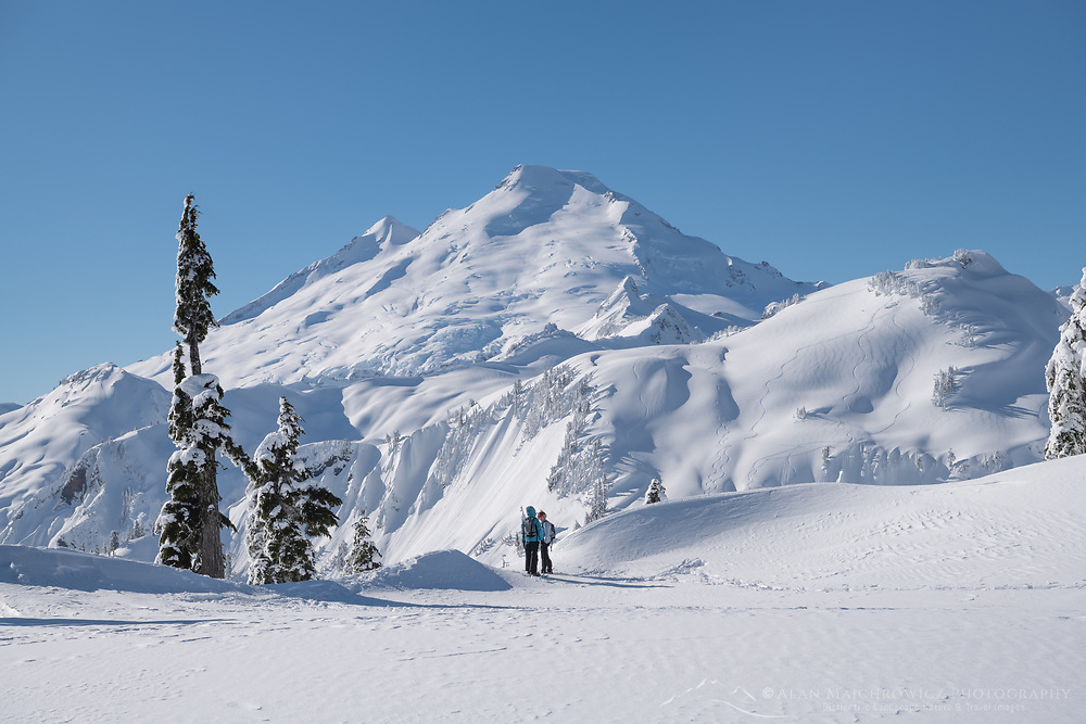Two backcountry skiers admiring view of Mount Baker from Artisit Point. North Cascades Washington