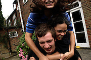 Lukats, 23, from Poland, (front), Kitty, 24, from Trinidad, (centre) and Josh, 25, from North London, (back) are playing on top of each others during a warm summer afternoon in the back garden of the Wildwood Road mansion on Saturday, Aug. 18, 2007, in Hampstead, London, England. Situated opposite Hampstead Heath, North London's green jewel the average price for properties on this road reaches £ 2,500,000. Million Dollar Squatters is a documentary project in the lives of a peculiar group of squatters residing in three multi-million mansions in one of the classiest residential neighbourhoods of London, Hampstead Garden. The squatters' enthusiasm, their constant efforts to look after what has become their home, their ingenuity and adventurous spirit have all inspired me throughout the days and nights spent at their side. Between the fantasy world of exclusive Britain and the reality of squatting in London, I have been a witness to their unique story. While more than 100.000 properties in London still lay empty to this day, squatting provides a valid, and lawful alternative to paying Europe's most expensive rent prices, as well as offering the challenge of an adventurous lifestyle in the capital.