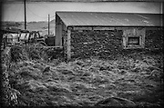 A tractor is parked outside a stone storage shed on a farm located near Inch Beach, Dingle Bay Peninsula.