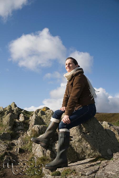 Mature woman sitting on a rock