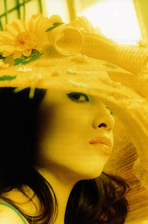 The face of an Asian woman wearing a yellow hat