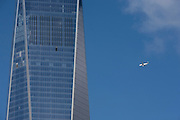 A jet aircraft flies past the newly-completed One World Trde Center (WTC) on what was Ground Zero on the September 11th 2001 attacks on New York City, USA