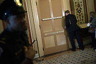 "An aide peeks in the committee room door as Democratic members of the 'super committee' wrap up a meeting at the U.S. Capitol in Washington. With a deadline less than a week away, members of a 12-member ""super committee"" tasked with finding $1.2 trillion in budget savings confronted the same barriers that have thwarted earlier efforts to rein in the growing national debt."