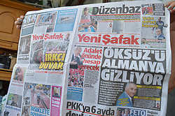 August 9, 2017 - Ankara, Turkey - A woman holds a today's copy of Turkish pro-government daily newspaper Yeni Safak in Ankara, Turkey on August 09, 2017. The daily claims on its front page with a headline that the German government hides Adil Oksuz, the key person of the July 15, 2016 failed coup attempt, in Germany. (Credit Image: © Altan Gocher/NurPhoto via ZUMA Press)