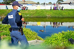 South Africa - Cape Town - 21 July 2020 - The body of Yusuf Kiroboto was found floating in the Blackriver just off the N2 close to Athlone. Gegeidu Omar Eka, to whom Yusuf was an Uncle, couldn't hold back his tears when he arrived on the scene and seeing his Uncle's body. Yusuf went missing after having been swept away by the river while trying to save a young girl that seemed to be drowning. People were pearing over walls and lined the river, watching the gruesome scene unfold. Picture Courtney Africa/African News Agency(ANA)