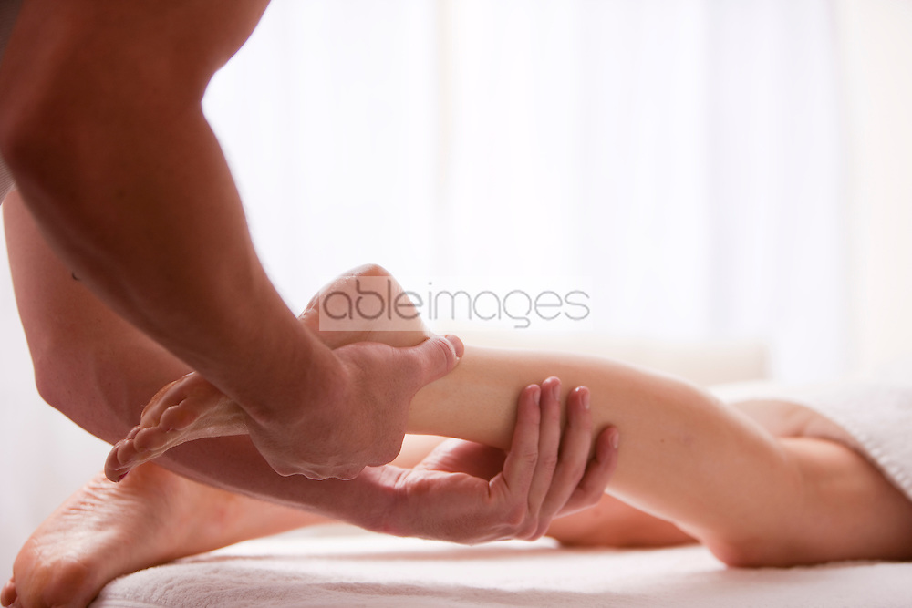 Close up of a masseur hands massaging a woman foot