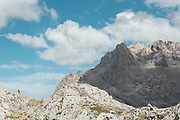 Trail runner running uphill in Collado Jermoso, Leon, Spain Trail runner running uphill in Collado Jermoso, Picos de Europa National Park, Spain