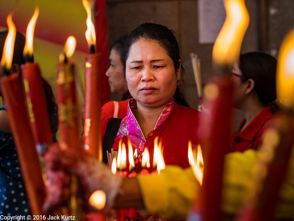 """08 FEBRUARY 2016 - BANGKOK, THAILAND: People make merit for Chinese New Year by lighting candles and incense at Wat Mangon Kamlawat, the largest Mahayana (Chinese) Buddhist temple in Bangkok during the celebration of the Lunar New Year. Chinese New Year is also called Lunar New Year or Tet (in Vietnamese communities). This year is the """"Year of the Monkey."""" Thailand has the largest overseas Chinese population in the world; about 14 percent of Thais are of Chinese ancestry and some Chinese holidays, especially Chinese New Year, are widely celebrated in Thailand.       PHOTO BY JACK KURTZ"""