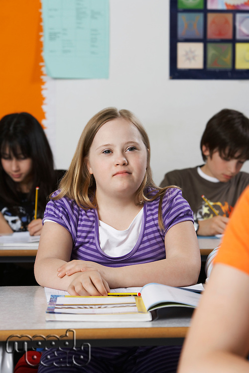 Girl (10-12) with Down syndrome in classroom portrait
