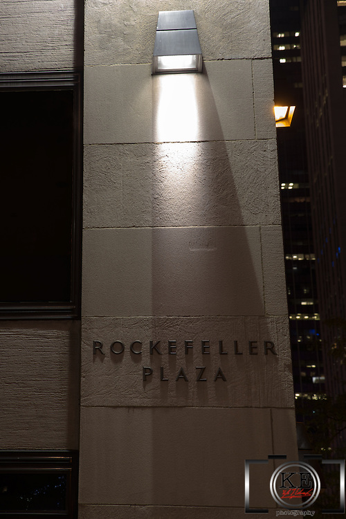Rockefeller Plaza sign, lit up by an overhead light at night.