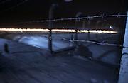 """Der Sicherheitszaun im ehemaligen Konzentrationslager Auschwitz Birkenau am Tag der Gedenkfeiern zur 60. Jährigen Befreiung des Konzentrationslagers durch die Rote Armee am 27. Januar 1945. Im Hintergrund die """"brennenden Gleise"""" am Ende der Gedenkfeiern. Das Feuer bewegt sich die Gleise entlang bis zum """"Tor des Todes"""" knapp einen Kilometer entfernt am anderen Ende des Lagers."""