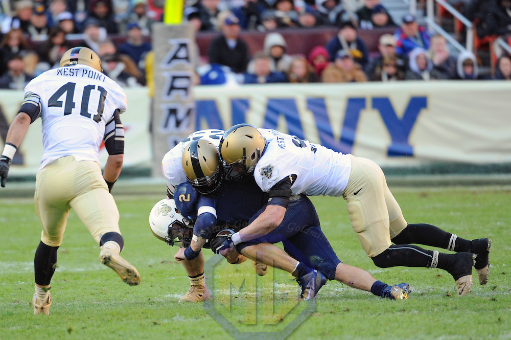 10 December 2011:   Navy Midshipmen quarterback Kriss Proctor (2) is brought down by Army Black Knights defensive back Thomas Holloway (23) and Army Black Knights linebacker Steven Erzinger (9) at Fed Ex field in Landover, Md. in the 112th annual Army Navy game where Navy defeated Army, 27-21 for the 10th consecutive time.
