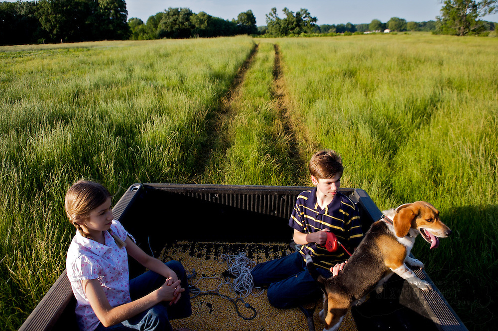 Photo by Gary Cosby Jr.  Kids ride in the back of their father's pickup truck with the family dog as they go to collect eggs on their farm in Morgan County, Alabama.