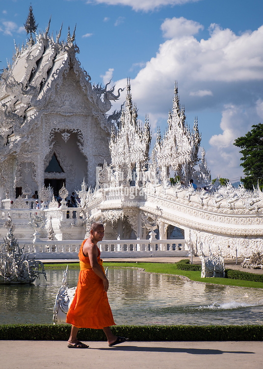 "A monk walks past Wat Rong Khun, the ""white temple"" outside of Chiang Rai in Northern Thailand."