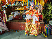 """26 NOVEMBER 2014 - BANGKOK, THAILAND:  A performer waits for the Chinese opera to start at the Chow Su Kong Shrine in the Talat Noi neighborhood of Bangkok. Chinese opera was once very popular in Thailand, where it is called """"Ngiew."""" It is usually performed in the Teochew language. Millions of Chinese emigrated to Thailand (then Siam) in the 18th and 19th centuries and brought their culture with them. Recently the popularity of ngiew has faded as people turn to performances of opera on DVD or movies. There are about 30 Chinese opera troupes left in Bangkok and its environs. They are especially busy during Chinese New Year and Chinese holidays when they travel from Chinese temple to Chinese temple performing on stages they put up in streets near the temple, sometimes sleeping on hammocks they sling under their stage.     PHOTO BY JACK KURTZ"""
