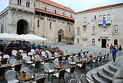 John Paul II Square (Trg Ivana Pavla II) filled with cafe tables and chairs, with Cathedral of Saint Lawrence (Katedrala sveti Lovre), and the City Hall (the Rector's Palace - Op?inska pala?a). Trogir, Croatia