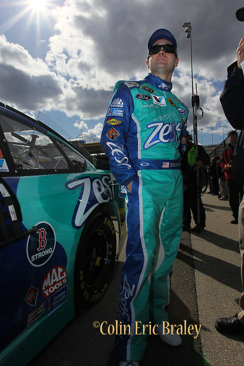 Rick Stenhouse Jr. stands next to a B Strong sticker, honoring the Boston bombing victims, after making his qualifying run for a NASCAR Sprint Cup race at Kansas Speedway, Friday, April 19, 2013 in Kansas City, Kansas. (AP Photo/Colin E. Braley)