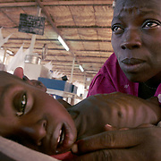 August 4, 2005 - Maradi, Niger - Tchima Mamane comforts her son, Rashid, age 2. He weighs 5.4 kg. Rashid got sick three months ago and came to the MSF feeding center six days ago where he was put in intensive care. He hasn't laughed for twenty days, Tchima says she'll be happy when he does because she knows he is better Maradi, Niger. Photo by Evelyn Hockstein/Polaris