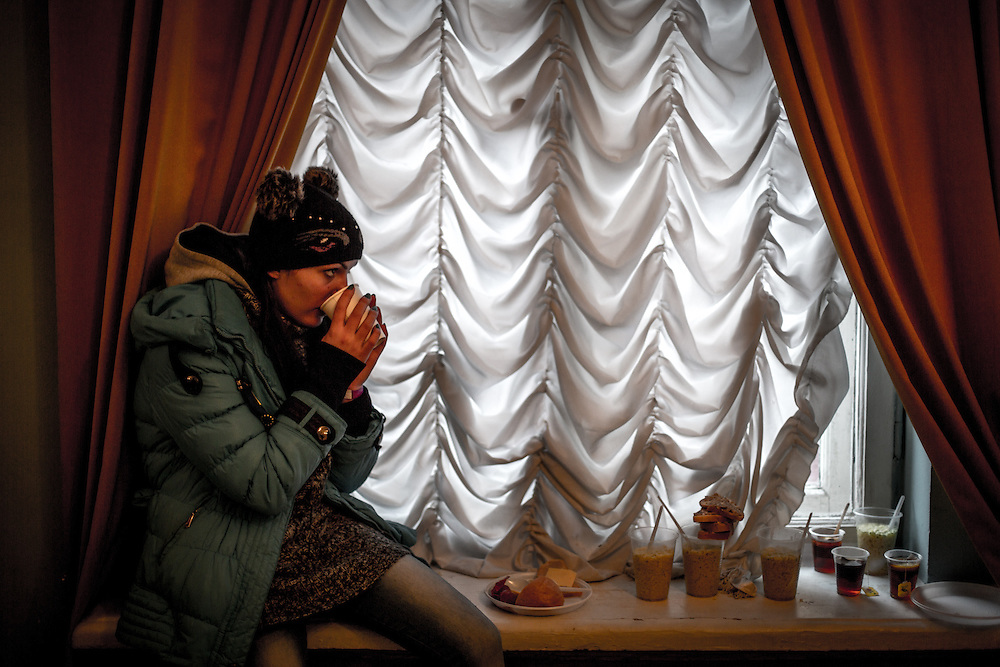 A young woman drinks a glass of tea, in the Center of Ukrainian Culture, occupied by the protesters.