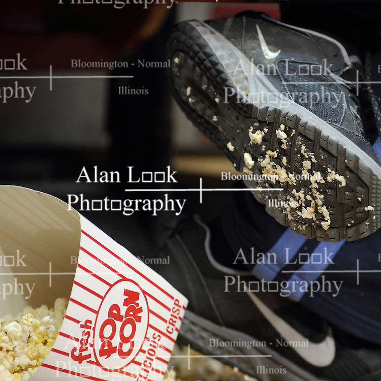 04 January 2015:  a spilled container of popcorn is distributed across the floor with some remaining in the container and some ground into the sole of a youngsters sneaker.
