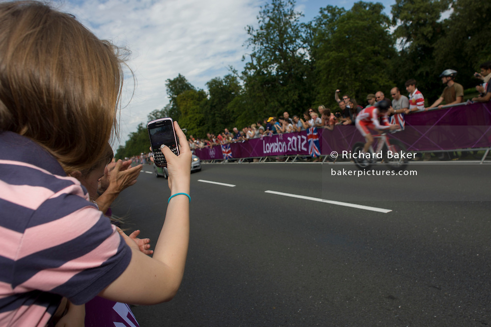A young girl uses her Blackberry Curve to films cyclists as they race past fans lining the route through Bushy Park in south west London, during the London 2012 Olympic 44km men's cycling time trial, eventually won by Team GB's Bradley Wiggins.