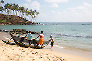 Tourist boy helping local men to launch their fishing canoe, Mirissa, Sri Lanka, Asia