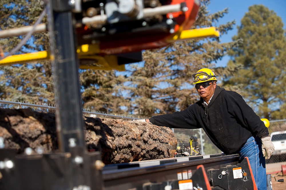 112712       Brian Leddy.Robert Catron helps with cutting boards on a new portable sawmill Tuesday. The Navajo Nation Forestry Department and plans to start cutting boards and will offer them for sale to the general public.