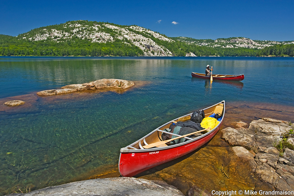 Canoeing on Killarney Lake with white quartzite rock of the La Cloche Hills in the background<br />