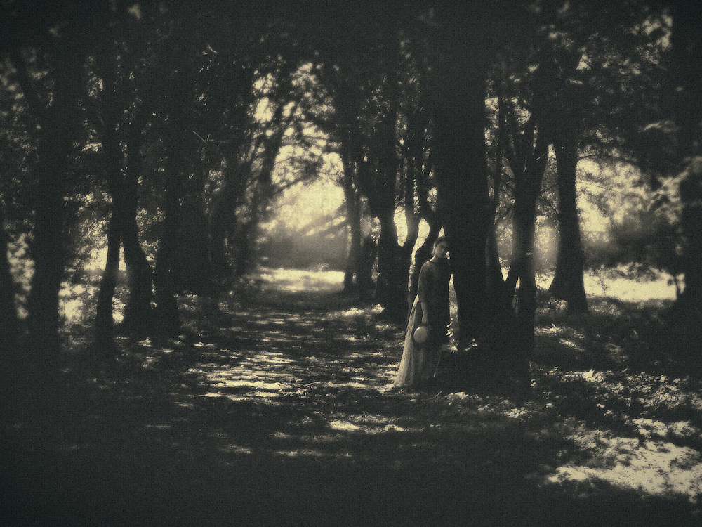 A woman in a vintage outfit, standing by a tree, on a path in an old park, with the sun setting behind the trees.