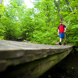 A hiker crossing a stream on Monadnock Mountain in Lemington, Vermont.  The Northeast Kingdom.